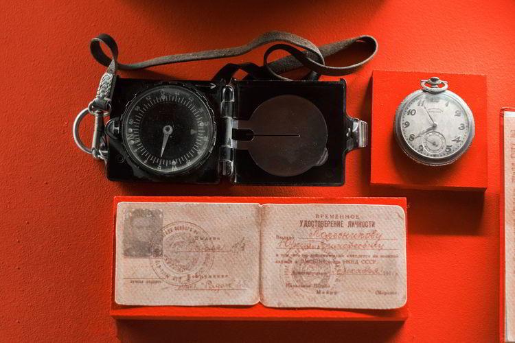 High angle view navigational compass and passport on table