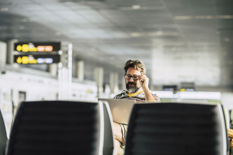Mature man using laptop while sitting at airport