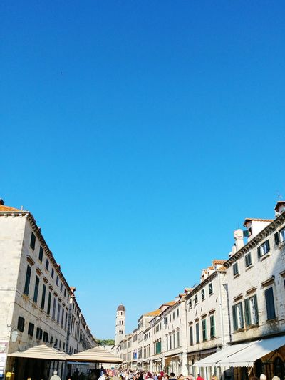 Low angle view of buildings by st saviour church against clear blue sky in city