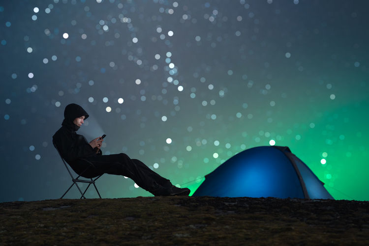 Side View Of Man Using Mobile Phone While Sitting On Field At Night
