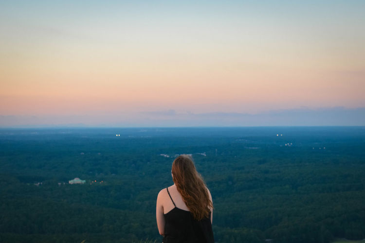 Rear view of woman standing over landscape against sky during sunset