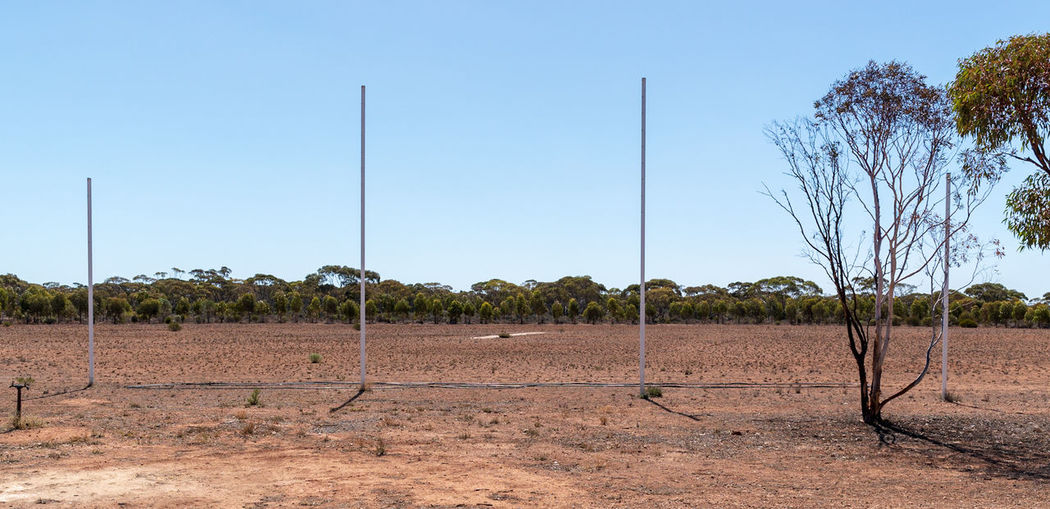 Thirsty Oval Goal Post Cricket Pitch Football Field Cricket Field Dry Red Dirt Tree Sky Arid Climate Barren Drought