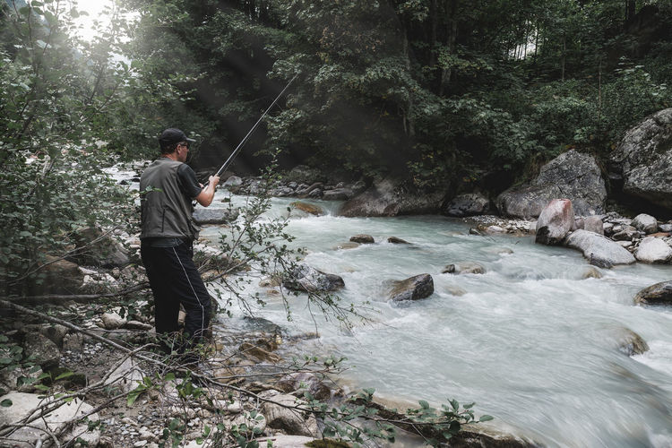 Full length of man fishing in forest