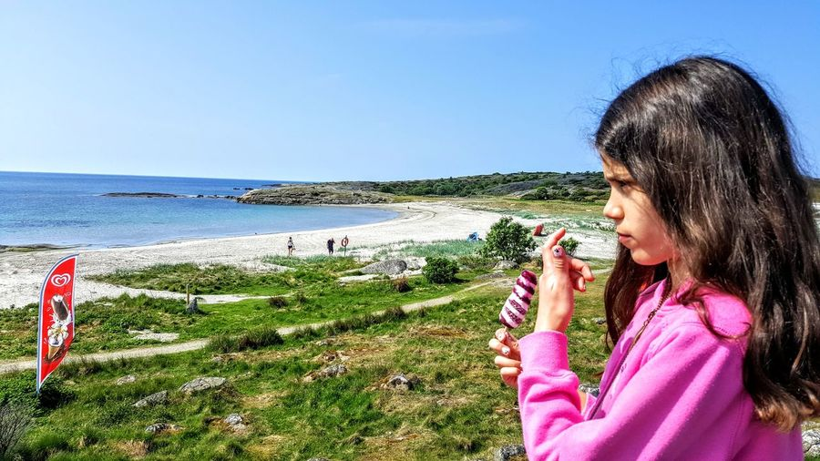 Girl holding ice cream while looking away at beach against clear blue sky