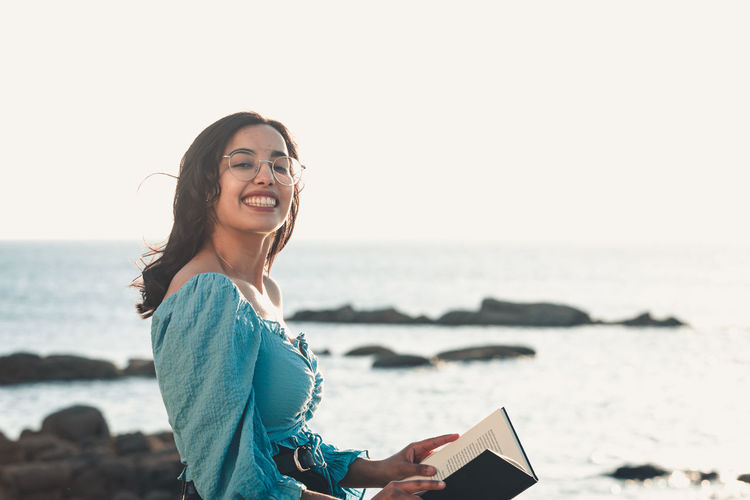 Portrait of young woman using phone on beach