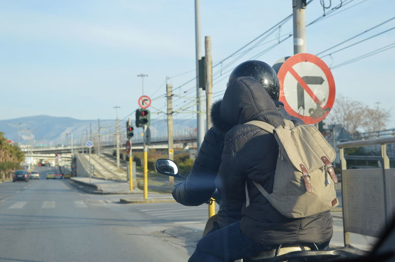 Couple Day Helmet Outdoors Protection Real People Rear View Road Road Sign Safety Sign Sky Street Transportation
