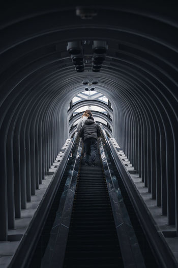 Rear view of man on escalator in tunnel
