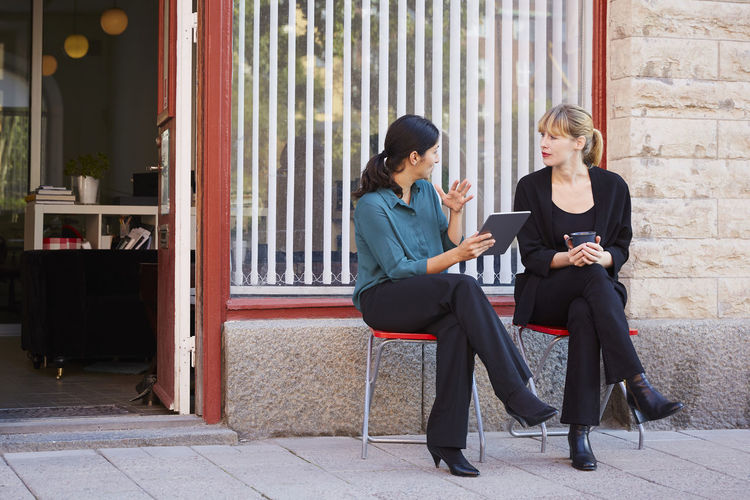 Young woman sitting on mobile phone in office