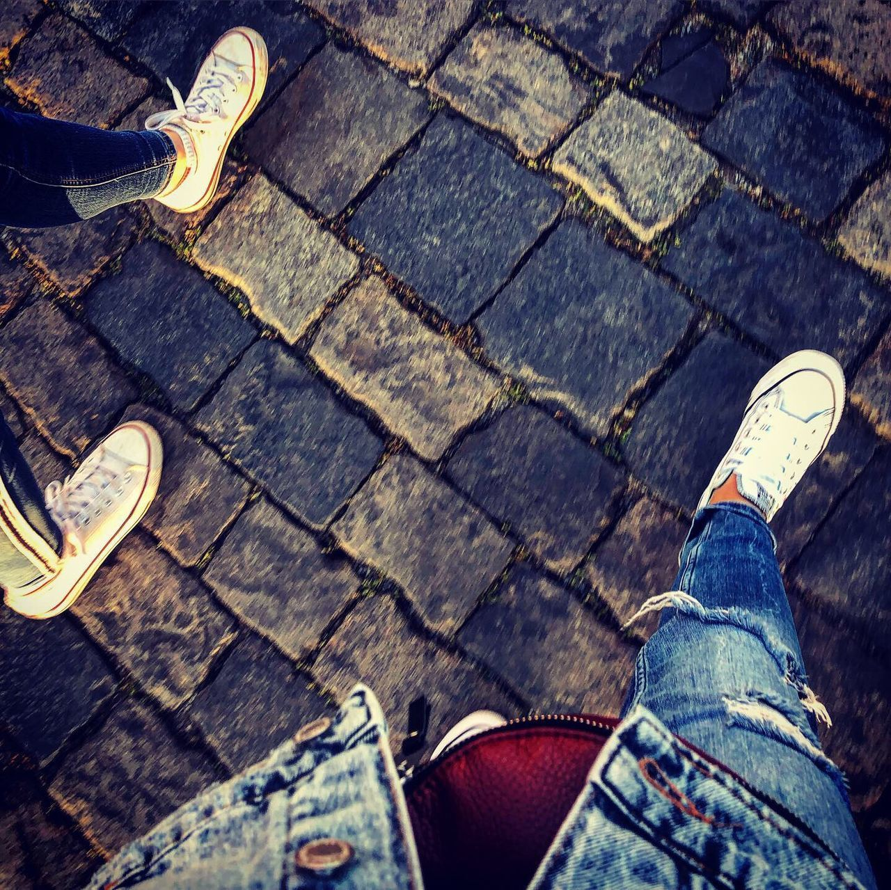 low section, shoe, human leg, human body part, body part, footpath, jeans, one person, personal perspective, street, real people, casual clothing, high angle view, lifestyles, city, leisure activity, standing, sidewalk, men, cobblestone, outdoors, paving stone, human limb, human foot