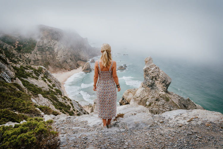 Rear view of woman on rock by sea against sky