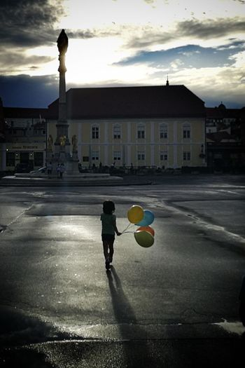 Man playing soccer ball in city