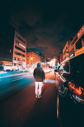 Rear view of man standing on street at night