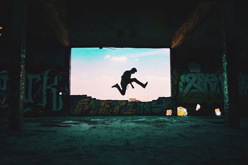Silhouette man jumping on built structure