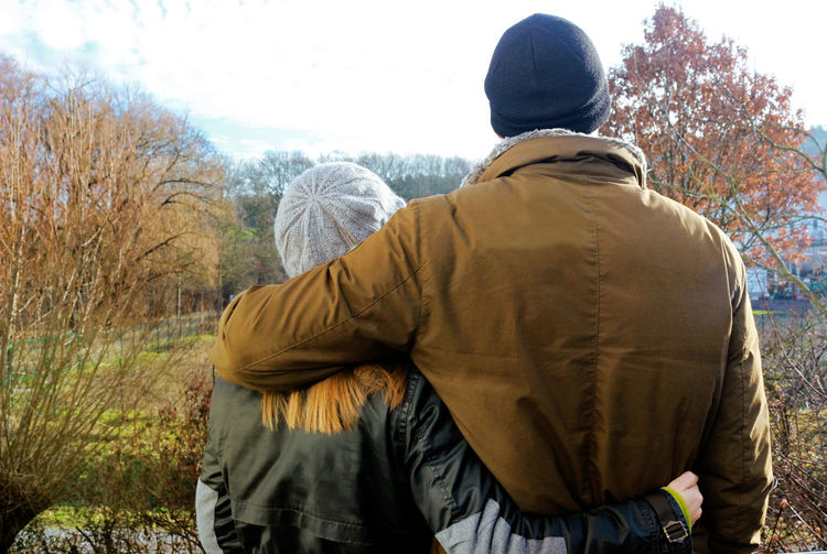 yong couple looking optimistic into future Rear View Real People Couple Lovers Arm In Arm Love Emotion Togethernessishappiness Winter Outdoors Day Adult Young Adult Woman Man Cap Long Hair Optimistic Hope Waist Up Standing Landscape Looking At Camera Tree Sunlight