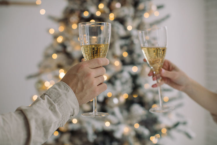 Cropped hand of couple holding champagne flutes against christmas tree at home