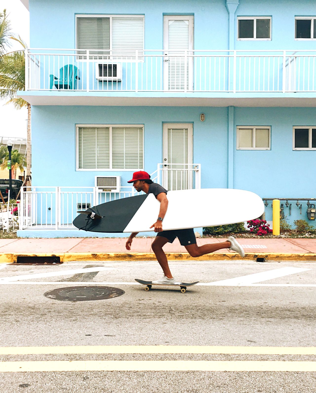 SIDE VIEW OF MAN SKATEBOARDING ON ROAD AGAINST BUILDINGS