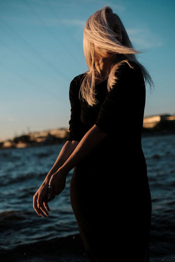 Side view of woman against sea at sunset