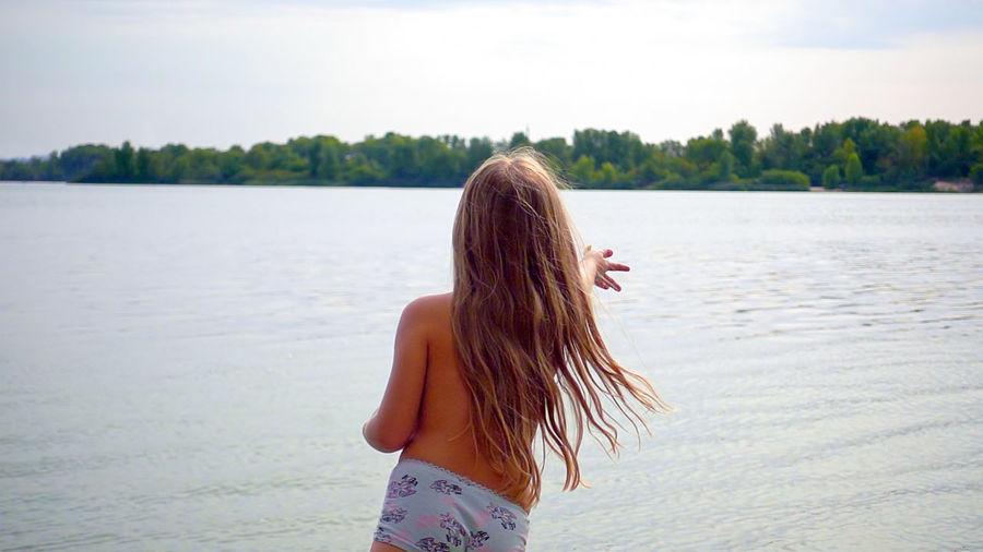 Shirtless Girl Throwing In Lake Against Sky
