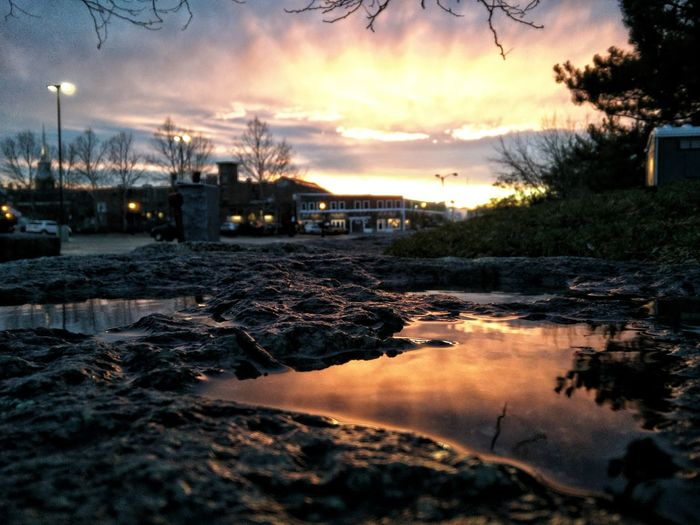 Puddle against sky during sunset