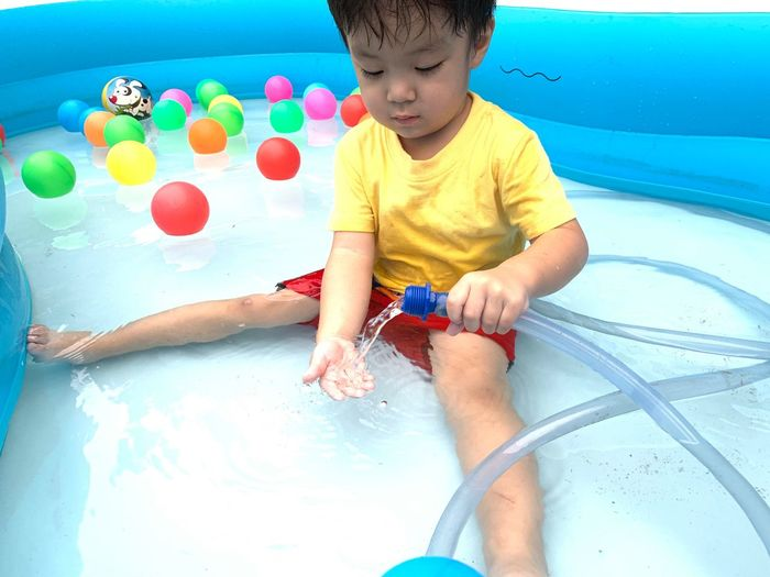 Childhood Child Real People One Person Leisure Activity Men Front View Water Lifestyles Boys Playing Males  Innocence Multi Colored High Angle View Cute Casual Clothing Outdoors Swimming Pool Shorts