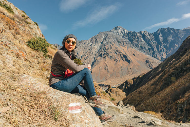 Portrait of young woman sitting on rock against mountains