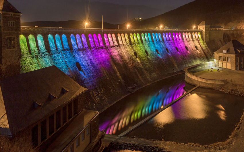 Illuminated bridge over canal in city at night