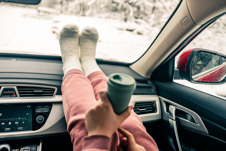 Low section of woman holding coffee cup sitting in car