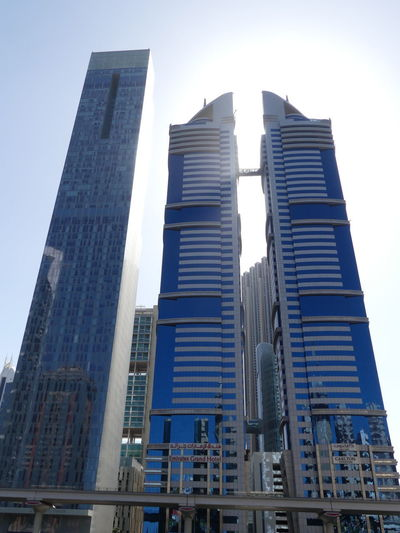 Emirates Grand Hotel (centre) & Carlton Hotel (right) on Sheik Zayed Road, Dubai, United Arab Emirates 2019 Dubai UAE 2019 Sheik Zayed Road No People Low Angle View Blue Sky Sunlight And Shade Skyscraper Tower Blocks Hotels Carlton Hotel City Tall - High Glass And Steel Structure Modern Architecture Modern Design Architecture Composition Outdoor Photography Metro Rail Steel And Glass Structure Building Exteriors Building Facades Tourist Destination