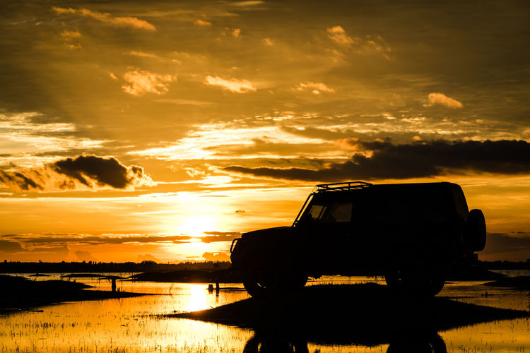 Silhouette Sport Utility Vehicle By Lake Against Cloudy Sky At Sunset