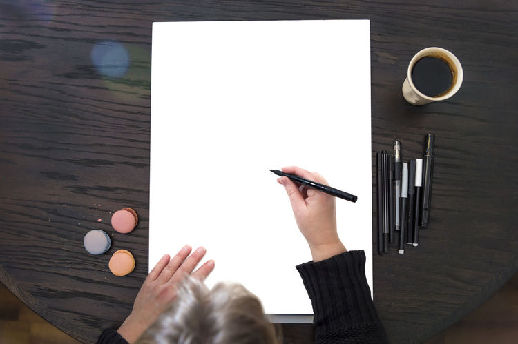 Background for creative pictures - person is starting to draw or write something Artist Center Coffee Copy Space Creativity Dark Macarons Macaroons Paper Woman Workplace Writing Background Block Cup Directly Above Drawing Felt Tip Pens Hand Lettering Human Body Part Painting Paper Pens person Table Modern Workplace Culture