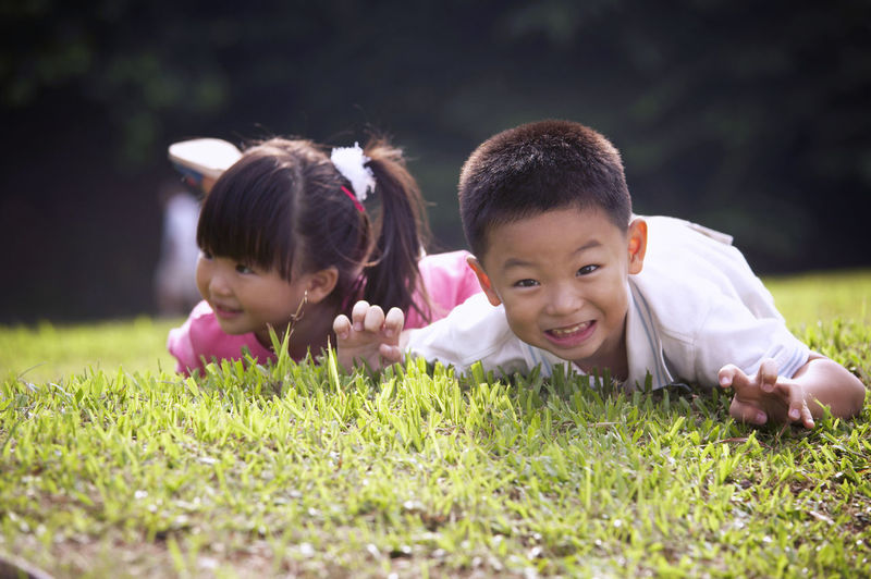 sibling playing at the park Brother Grass Hanging Out Sister Bonding Boy Child Childhood Cute Day Elementary Age Garden Girls Innocence Leisure Activity Lifestyles Looking At Camera One Person Outdoors Park - Man Made Space Playing Real People Sibling Smiling Two People