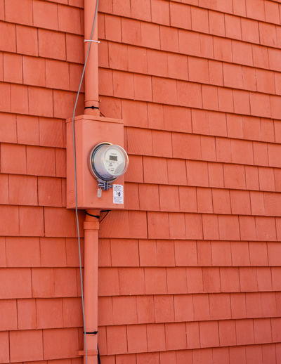 An old red round digital electricity meter on cedar shingles in Charlottetown, Prince Edward Island, Canada Wall - Building Feature Built Structure Brick Wall Brick Wall Architecture Technology Day No People Low Angle View Security Camera Pattern Building Exterior Outdoors Protection Close-up Meter - Instrument Of Measurement Old-fashioned Old Vintage City Wooden Wood Square Shape Round Shape Shape Colorful Colors Daylight Electricity Meter Electricity  Clock Blue Color Electrical Equipment Object House Building Home White Color Metal Cedar Shingles Wall