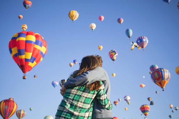 Low angle view of couple embracing against hot air balloons flying in sky