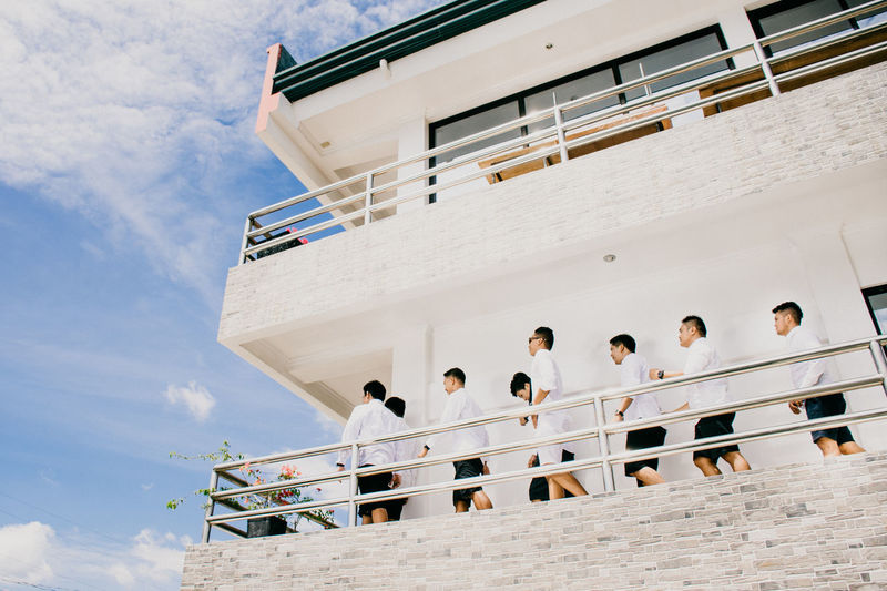 Low angle view of people on wall against sky