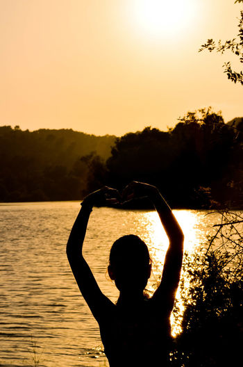 Rear view of silhouette person in lake against sky during sunset