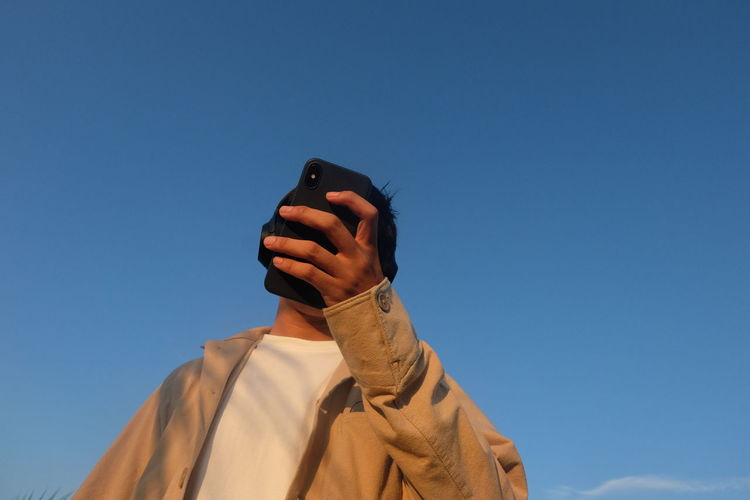 Low angle view of person photographing against blue sky