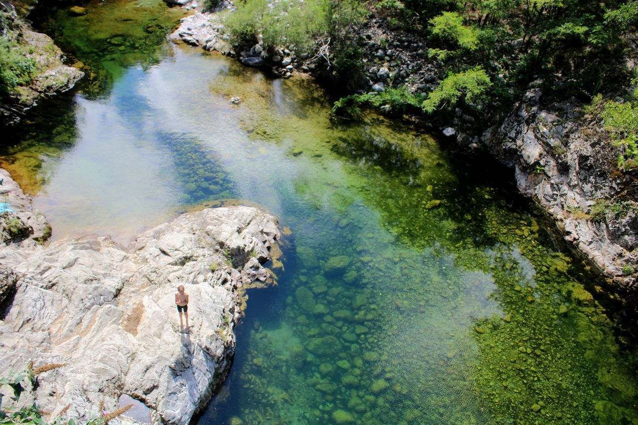 HIGH ANGLE VIEW OF WATER FLOWING THROUGH ROCKS IN LAKE