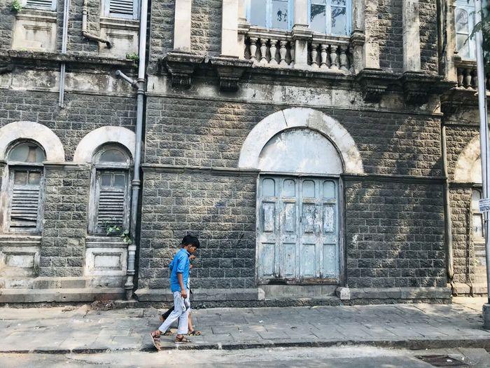 Full length of boy standing against building