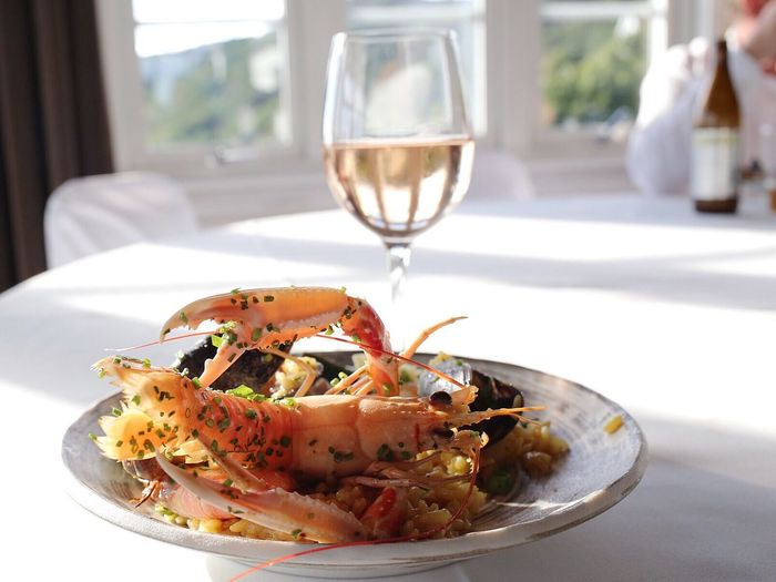 Close-up of paella served with white wine on table in restaurant