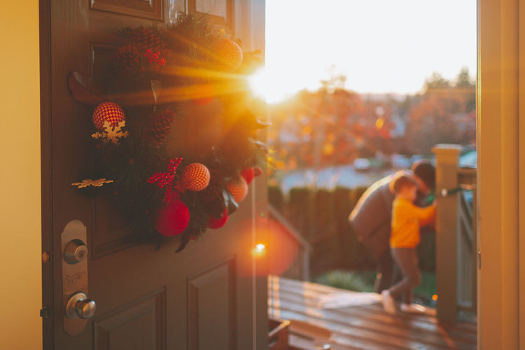 A father and son putting up Christmas lights, as a wreath hangs on the door. Focus On Foreground Day Door Outdoors Sunlight Wreath Christmas Father Man Boy Son Decorating Home House