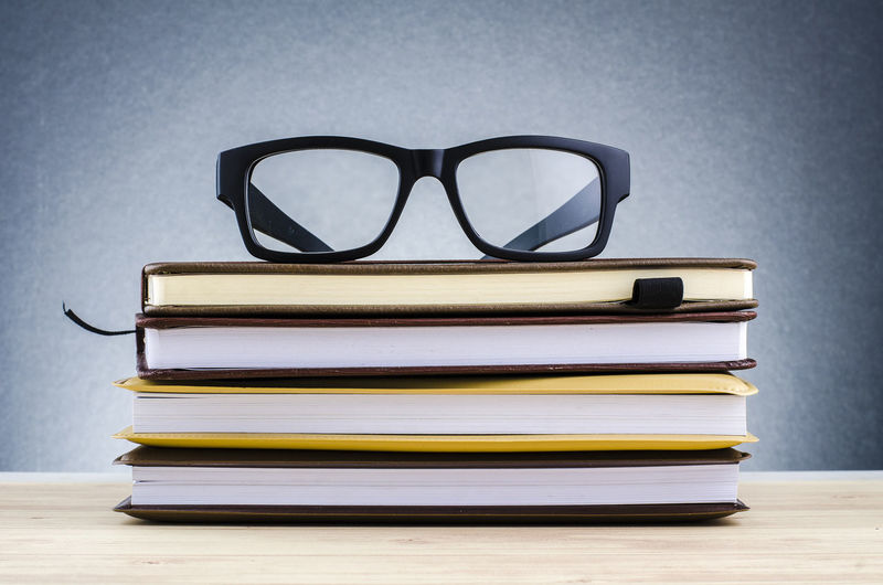 spectacles on stack of books over beautiful gradient background with reverberation Stack Publication Book Glasses Education Table Eyeglasses  Indoors  No People Still Life Close-up Sunglasses Learning Reading Glasses Focus On Foreground Wisdom Literature Absence Paper Personal Accessory Eyewear Hardcover Book