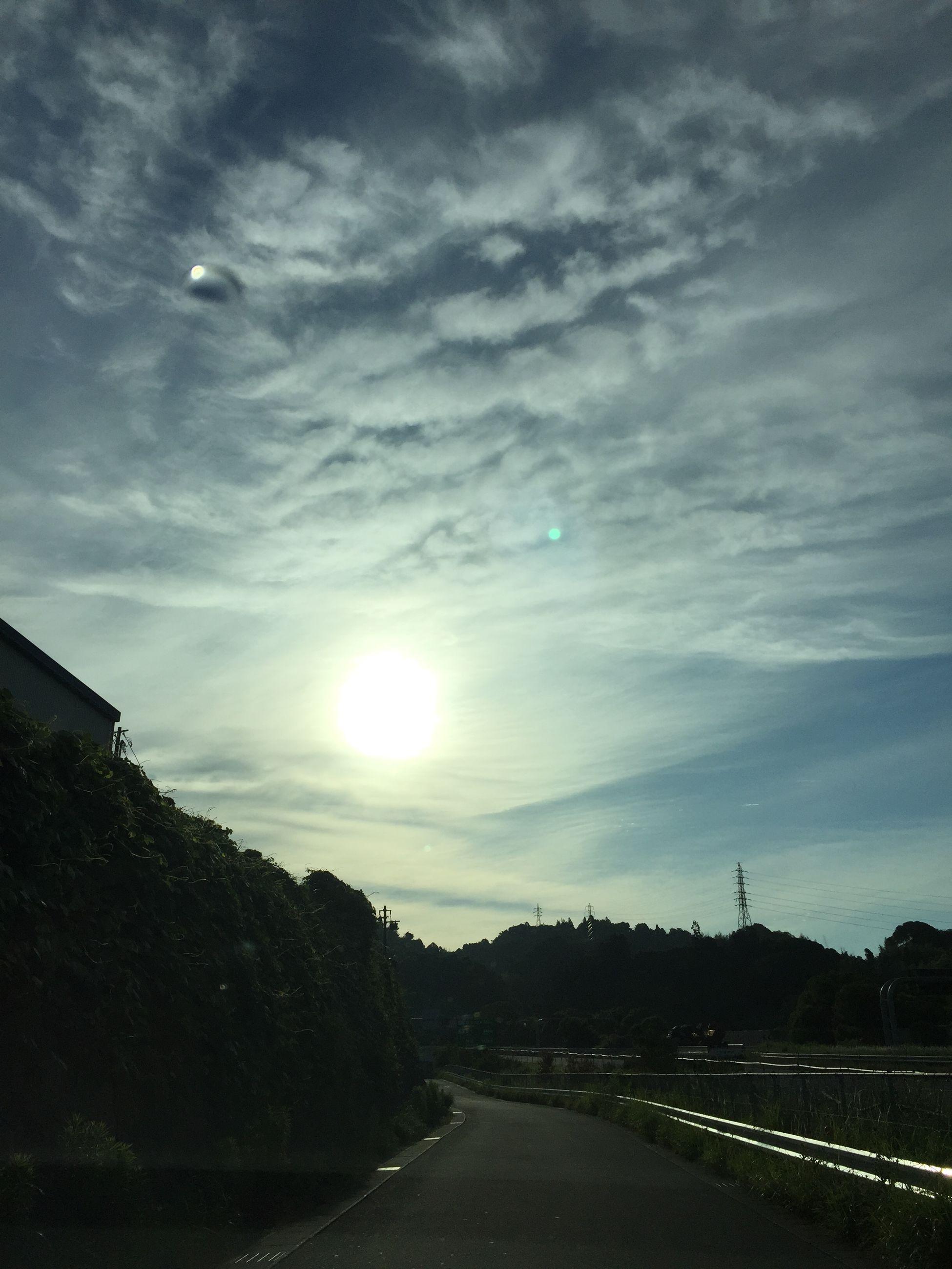 sky, building exterior, sun, built structure, architecture, cloud - sky, sunset, sunlight, lens flare, sunbeam, transportation, cloud, low angle view, street, silhouette, outdoors, nature, cloudy, city, building