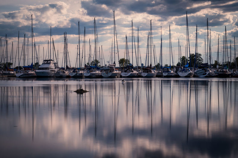 Boats Moored At Harbor Against Cloudy Sky At Dusk