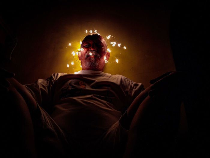 Low angle view of man sitting amidst illuminated string lights against wall