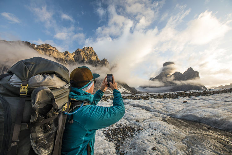 Man photographing on rock against sky during winter