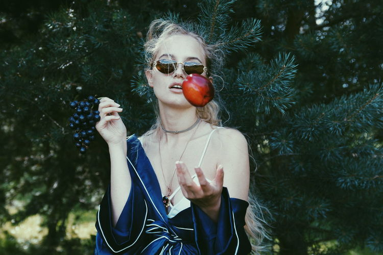 Woman Throwing Apple Against Trees
