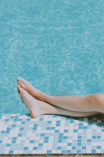 Low section of woman lying on swimming pool