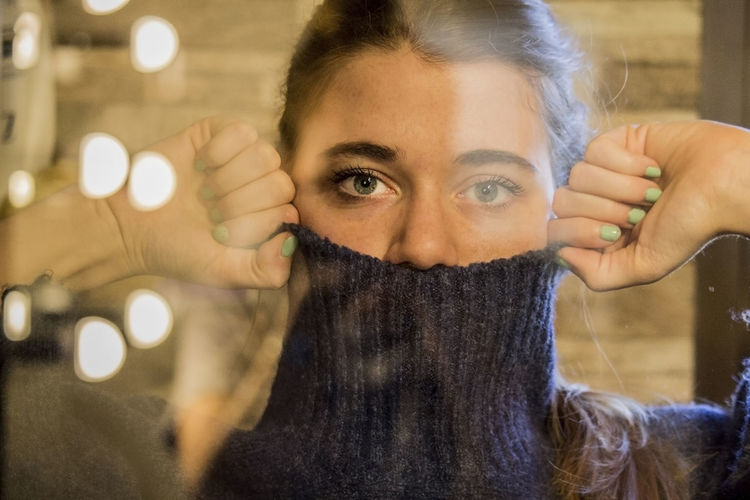 Portrait Of Woman Covering Face With Turtleneck Sweater Seen Through Glass