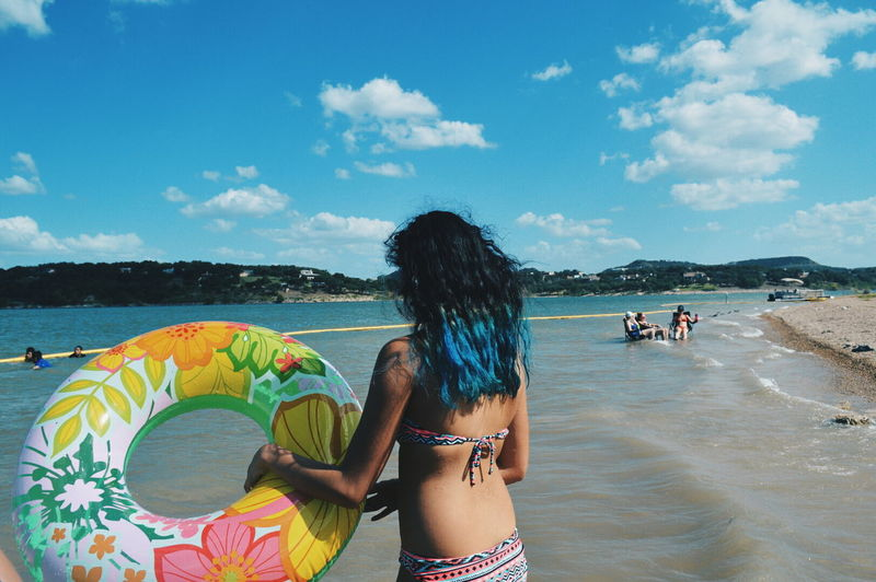 Rear View Of Young Woman In Bikini Carrying Inflatable Ring At Beach