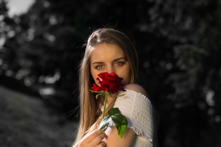 Close-up portrait of young woman holding red rose